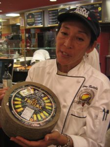Lynn Battels with a wheel of cheese.