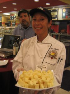 Lynn Battels displaying the Grafton Village Farms Classic Reserve Cheddar with David Hall behind her.